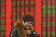 Un inversor sonríe frente a un tablero electrónico que muestra la información de las acciones, en una correduría en Fuyang, China, 21 de diciembre de 2015. El referencial CSI300 de las principales acciones que cotizan en Shanghái y Shenzhen saltó el lunes a un máximo de cuatro meses, liderado por repuntes en los papeles ligados al sector inmobiliario y la banca. REUTERS/Stringer ATENCIÓN EDITORES - ESTA IMAGEN FUE PROVISTA POR UNA TERCERA PARTE.SÓLO DISPONIBLE PARA USO EDITORIAL. ESTA IMAGEN ES DISTRIBUIDA EXACTAMENTE COMO FUE RECIBIDA POR REUTERS,COMO UN SERVICIO A LOS CLIENTES