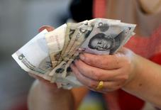 A vendor holds Chinese Yuan notes at a market in Beijing in this August 12, 2015 file photo.   REUTERS/Jason Lee/Files