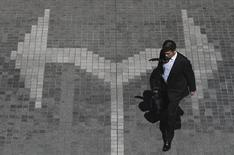 A man walks on a traffic sign in the taxi stand of a building at a business district in Tokyo, March 17, 2015. REUTERS/Yuya Shino