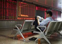 El banco central de China suspendió temporalmente algunas operaciones de cambio de divisas de varios bancos extranjeros hasta finales de marzo, dijeron el miércoles a Reuters tres fuentes con conocimiento directo de la situación. En la imagen, un inversor frente a una pizarra de cotizaciones en un broker en Pekín el pasado 12 de octubre. REUTERS/Stringer