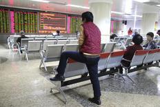 Las bolsas chinas bajaron el lunes un 7 por ciento en su primera sesión de 2016 debido a unos sondeos que mostraron débiles datos manufactureros y una caída del yuan que se sumó a las preocupaciones sobre la economía, forzando a las bolsas a suspender la cotización por primera vez. En la imagen, un inversor mira una pantalla electrónica con cotizaciones, en Pekín, el 4 de enero de 2016.  REUTERS/Li Sanxian