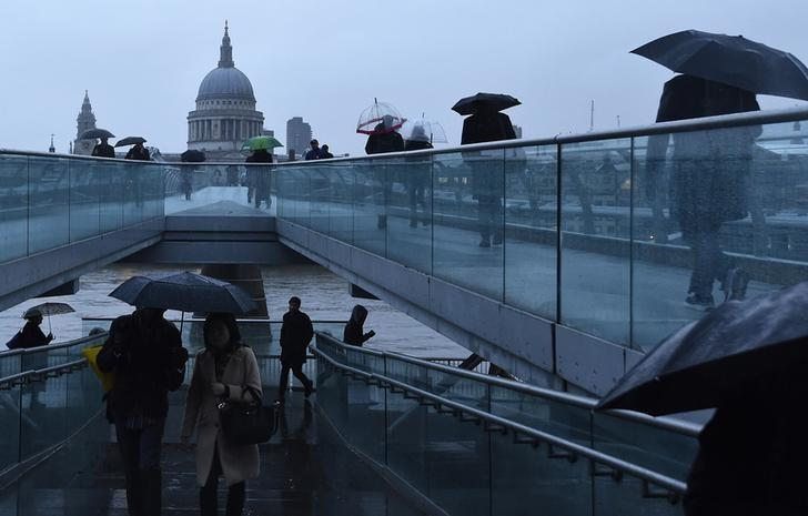 City workers cross the Millennium footbridge at dawn in front of St Paul's Cathedral in London, Britain January 7, 2016.  REUTERS/Toby Melville