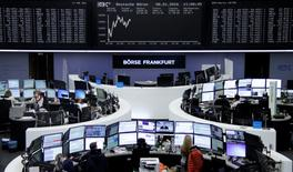 Traders work at their desks in front of the German share price index, DAX board, at the stock exchange in Frankfurt, Germany, January 8, 2016.     REUTERS/Staff/Remote