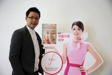 Wattanapak Jinsirivanich, managing director of Yulihan Group (Thailand), the company that produces Seoul Secret beauty products, poses next to an ad for Seoul Secret Collagen Peptide during an interview with Reuters in Bangkok January 9, 2016. REUTERS/Jorge Silva