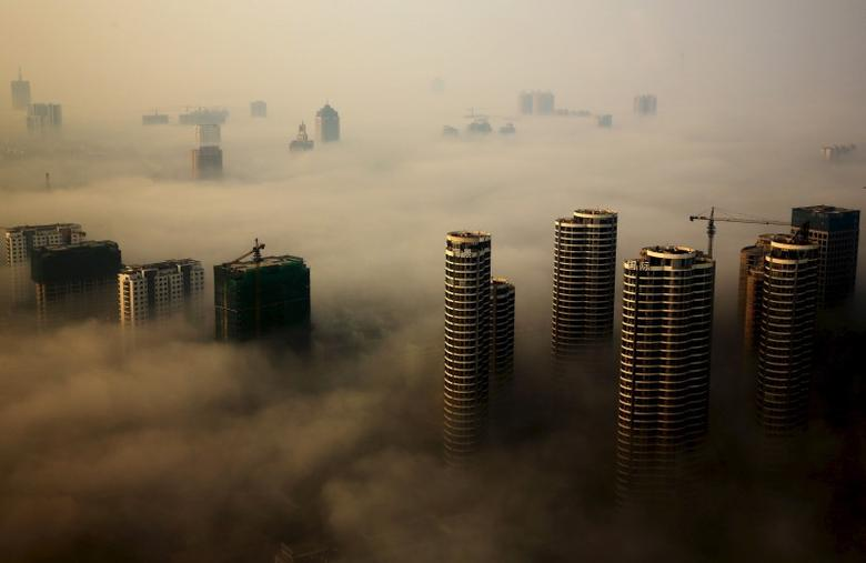 Buildings in construction are seen among mist during a hazy day in Rizhao, Shandong province, China, October 18, 2015. REUTERS/Stringer CHINA OUT.