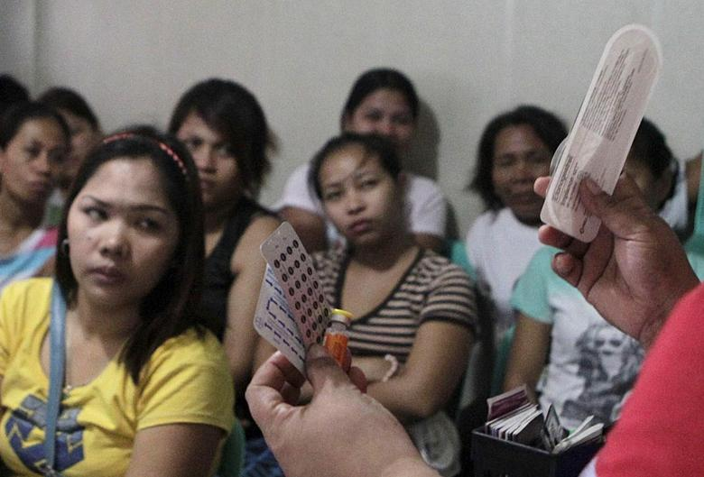 A community health worker holds up contraceptives during a lecture on family planning at a reproductive health clinic run by an Non-Governmental Organization (NGO) in Manila January 12, 2016.   REUTERS/Janis Alano