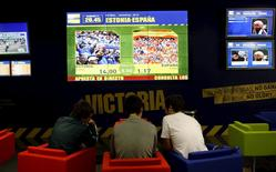 Customers prepare their sporting bets at the betting shop Victoria in Madrid in this October 11, 2008 file photo.  REUTERS/Susana Vera/Files