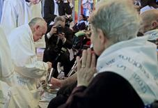 Pope Francis kisses a foot of a disabled person at the S. Maria della Provvidenza church in Rome, during a Holy Thursday celebration, in this April 17, 2014 file photo. REUTERS/Tony Gentile/Files