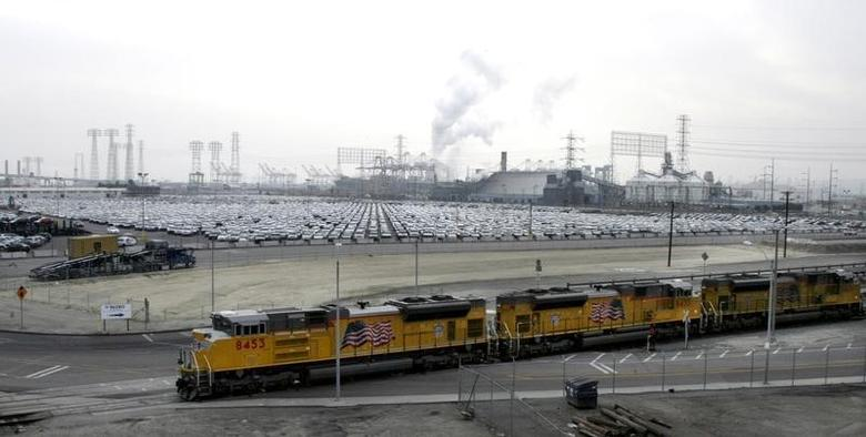 A set of Union Pacific freight locomotives roll past a holding lot with Toyota automobiles at the Port of Long Beach in California December 4, 2008.  REUTERS/Fred Prouser