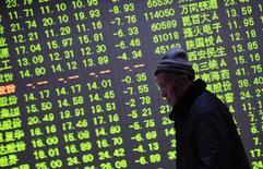 El rebote del precio del petróleo sirvió de catalizador para que el Ibex-35 de la bolsa española cerrara en positivo, gracias al empuje de la banca y los valores ligados a las materias primas como la petrolera Repsol y las acereras.  En la imagen, un inversor pasa por delante de una pantalla electrónica con información sobre precios bursátiles en una casa de valores en Hangzhou, provincia de Zhejiang, 21 de enero de 2015. REUTERS/China Daily