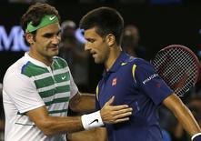 Serbia's Novak Djokovic (R) and Switzerland's Roger Federer shake hands at the net after Djokovic won their semi-final match at the Australian Open tennis tournament at Melbourne Park, Australia, January 28, 2016. REUTERS/Tyrone Siu
