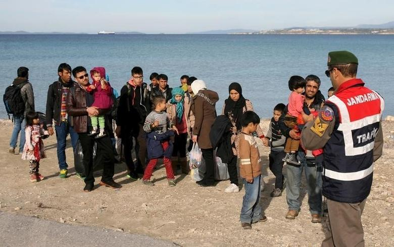 A Turkish Gendarme leads a group of refugees to buses to prevent them from sailing off for the Greek island of Chios by dinghies, at a beach in the western Turkish coastal town of Cesme, in Izmir province, Turkey, December 1, 2015. REUTERS/Denizhan Guzel