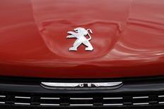 A logo is pictured on a Peugeot 208 car parked at the PSA Peugeot Citroen plant in Poissy, near Paris, France, April 29, 2015.     REUTERS/Benoit Tessier