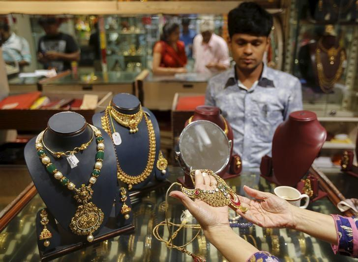 A customer tries a gold necklace at a jewellery showroom on the occasion of Dhanteras, a Hindu festival associated with Lakshmi, the goddess of wealth, at a market in Mumbai, India, November 9, 2015. REUTERS/Shailesh Andrade/Files