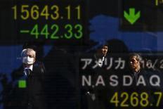 Personas se reflejan en una pantalla que muestra índices de mercados, afuera de una correduría en Tokio, Japón, 10 de febrero de 2016. Las bolsas de Asia caían el miércoles en medio de la preocupación creciente sobre la salud de los bancos del mundo, particularmente en Europa, que llevaba a los inversores hacia los activos más seguros como el yen, que operaba cerca de un máximo en 15 meses frente al dólar. REUTERS/Thomas Peter