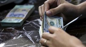 Un empleado contando dólares en una casa de cambios en Hanoi, ago 12, 2015. El dólar intentaba recuperarse de mínimos de tres meses y medio el miércoles, ante el temor a una ralentización de la economía global, mientras que operadores aguardaban las declaraciones de la presidenta de la Fed, Janet Yellen, en busca de nuevas pistas sobre el curso de las tasas de interés en Estados Unidos.  REUTERS/Kham