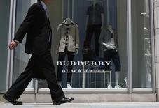 Прохожий у магазина Burberry в Токио. 12 мая 2014 года. Против британского ритейлера одежды и аксессуаров премиум-класса Burberry в США выдвинут коллективный иск, в котором компанию обвиняют в использовании в стоковых магазинах вводящих в заблуждение ценников, заставляющих покупателей думать, что им предоставляется большая скидка. REUTERS/Yuya Shino