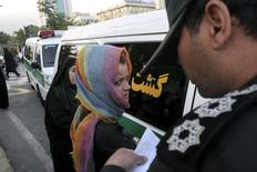 """Morality police take down the name of a detained woman during a crackdown on """"social corruption"""" in north Tehran in this June 18, 2008 file photo.  REUTERS/Stringer/Files"""