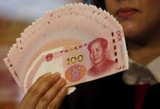 Una persona muestra la edición 2015 del billete de 100 renminbis en Hong Kong, China, 12 de noviembre de 2015. REUTERS/Bobby Yip