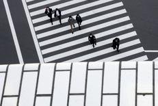 People cross a street in a business district in Tokyo, Japan, February 16, 2016. REUTERS/Thomas Peter