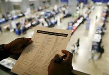 Una persona revisa un folleto en una feria laboral en Washington, ene 8, 2016. El número de estadounidenses que presentaron nuevas solicitudes de subsidios por desempleo cayó inesperadamente la semana pasada, lo que apunta a una fortaleza en el mercado laboral que podría mantener sobre la mesa nuevas alzas de las tasas de interés por parte de la Reserva Federal este año.      REUTERS/Gary Cameron