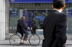 Un hombre en bicicleta pasa delante de un tablero electrónico que muestra la información de los índices de mercado de varios países, afuera de una correduría en Tokio, Japón, 4 de febrero de 2016. Las bolsas de Asia retrocedían el viernes desde máximos en cerca de tres semanas luego de que un avance de los precios del petróleo se revirtió y en momentos en que los inversores se muestran cautelosos sobre las perspectivas de la economía mundial. REUTERS/Yuya Shino