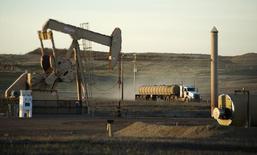 Грузовик у станка-качалки в Северной Дакоте 1 ноября 2014 года. Цены на нефть снижаются, так как Саудовская Аравия исключила возможность сокращения добычи, а запасы нефти в США выросли. REUTERS/Andrew Cullen