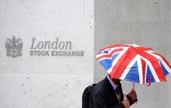 Человек проходит мимо здания Лондонской фондовой биржи 1 октября 2008 года. Европейские фондовые рынки увеличили добытое на предыдущей сессии преимущество, достигнув месячного пика во вторник на фоне роста акций London Stock Exchange после того, как Intercontinental Exchange подтвердила возможное контрпредложение о покупке финансовой компании. REUTERS/Toby Melville