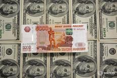 Рублевые и долларовые купюры в Сараево 9 марта 2015 года. Рубль достиг максимума текущего года, 72,57, в паре с долларом после выхода трудовой статистики США, оказавшейся лучше прогнозов и ускорившей рост нефти. REUTERS/Dado Ruvic