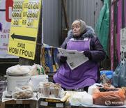 Продавщица читает газету у пункта обмена валюты в Киеве 3 марта 2016 года. Инфляция на Украине замедлилась в феврале 2016 года до 32,7 процента в годовом выражении с 40,3 процента в предыдущем месяце, сообщила Государственная служба статистики в среду. REUTERS/Gleb Garanich