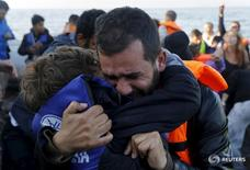 A Syrian refugee embraces his son after their overcrowded raft landed at a rocky beach in the Greek island of Lesbos, November 19, 2015. Balkan countries have begun filtering the flow of migrants to Europe, granting passage to those fleeing conflict in the Middle East and Afghanistan but turning back others from Africa and Asia, the United Nations and Reuters witnesses said on Thursday. REUTERS/Yannis Behrakis - RTS7Z6J