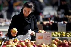 Una mujer compra manzanas en un mercado de agricultores, en Union Square, Nueva York. 20 de febrero de 2012. Los precios al productor de Estados Unidos bajaron en febrero por una caída de los costos de la energía y los alimentos, pero no mostraron cambios respecto del mismo mes del 2015, sugiriendo que la tendencia al descenso se acerca a su final. REUTERS/Andrew Burton