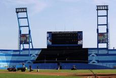 """Workers are seen at the Latinoamericano baseball stadium ahead of an exhibition baseball game between the Cuban national team and U.S. team Tampa Bay Rays, in Havana, Cuba March 16, 2016. The photographs show Cuban baseball legends Santiago """"Changa"""" Mederos (L) and Pedro Chavez and the writings underneath the photographs read """"Steadfast"""" (L) and """"Dignified.""""  REUTERS/Enrique De La Osa"""