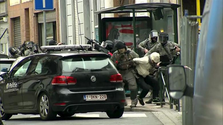Armed Belgian police apprehend a suspect, in this still image taken from video, in Molenbeek, near Brussels, Belgium, March 18, 2016. REUTERS/VTM via Reuters Tv