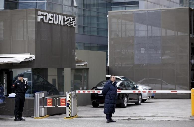 Security personnel stand guard at an entrance of the headquarters of Fosun International, in Shanghai, China, December 14, 2015. RETUERS/Aly Song - RTX1YJYV