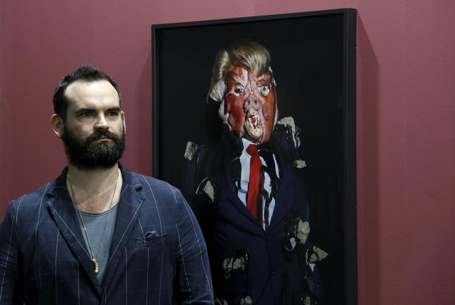 British artist James Ostrer poses beside a photo taken by him of his creation entitled ''Emotional Download'', which depicts Republican U.S. presidential candidate Donald Trump, as part of his series ''The Ego System'', during an art exhibition in Hong Kong, China March 23, 2016.      REUTERS/Bobby Yip