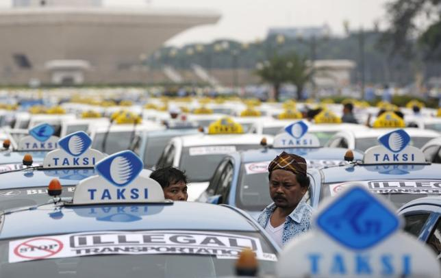 Taxis are seen parked near the National Monument as their drivers take part in a protest against what they say is unfair competition from ride-hailing services, in Jakarta, Indonesia March 14, 2016.  REUTERS/Darren Whiteside