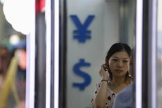 Женщина у пункта обмена валюты в Шанхае 14 августа 2015 года. Доллар США вырос до максимума одной недели к корзине валют в четверг, поскольку инвесторы ждут порцию статистики, которая смогла бы подтвердить достаточно оптимистичные взгляды ряда членов ФРС на американскую экономику. REUTERS/Aly Song