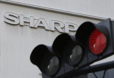 Светофор на фоне логотипа Sharp Corp. Токио, 26 февраля 2016 года. Sharp Corp сообщила, что ее годовая прибыль окажется ниже ее собственных официальных прогнозов, сославшись на замедление в Китае. REUTERS/Yuya Shino