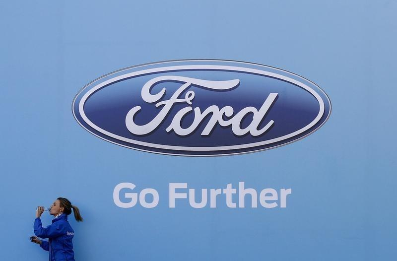 A Woman Has Drink As She Walks Past Logo Of Carmaker Ford At The Entrance To Media Event For Launch Concept Car In Sydney August 13
