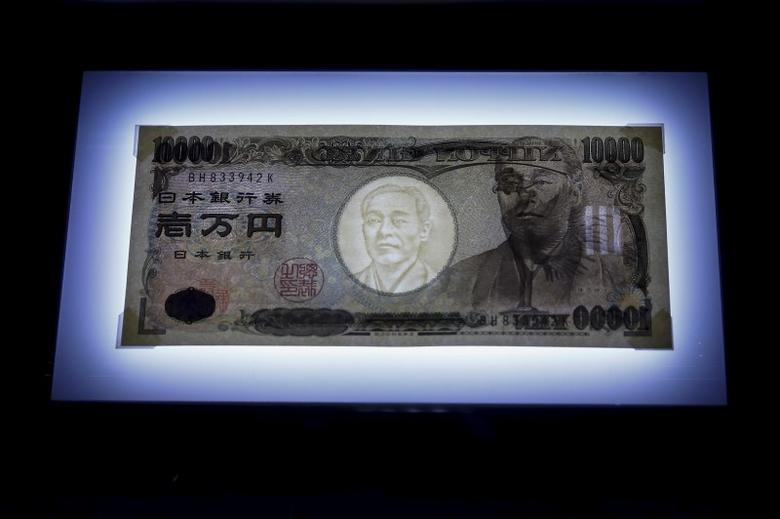 A 10,000 yen bill is seen on display on top of a light panel to make its security features visible at the Currency Museum of the Bank of Japan in Tokyo, November 18, 2015. Picture taken November 18, 2015.  REUTERS/Thomas Peter
