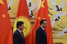 Премьер Киргизии Темир Сариев (слева) и китайский премьер Ли Кэцян в Пекине 16 декабря 2015 года. Президент Киргизии в понедельник принял отставку правительства, сложившего полномочия на фоне обвинений со стороны парламентариев в коррупции и лоббировании интересов Китая. REUTERS/Greg Baker/Pool