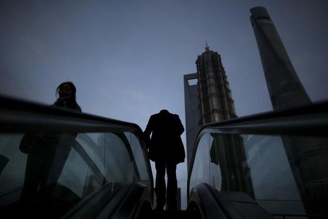 People ride escalators in the financial district of Pudong in Shanghai, China, March 15, 2016. REUTERS/Aly Song