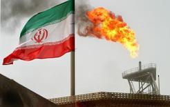 Флаг Ирана на нефтегазовой платформе в Персидском заливе. 25 июля 2005 года. Представители Ирана не будут участвовать во встрече нефтедобывающих стран, посвященной обсуждению заморозки уровня производства, в Дохе в воскресенье, 17 апреля, сказали Рейтер два источника, знакомых с ситуацией. REUTERS/Raheb Homavandi