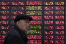 Инвестор идет мимо табло с информацией об акцией в брокерской компани в Шанхае.  Фондовый рынок Китая завершил торги понедельника снижением основных индексов на фоне резкого падения цен на нефть, подорвавшего уверенность инвесторов. REUTERS/Aly Song