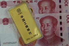 Una barra de oro fotografiada junto a billetes de 100 yuanes chinos, en esta fotografía ilustrativa tomada el 13 de abril de 2016. China, el mayor consumidor mundial de oro, lanzó el martes un referencial del metal precioso denominado en yuanes, una medida del país para ejercer un mayor control sobre el precio del metal y aumentar su influencia en el mercado mundial de los lingotes. REUTERS/Kim Kyung-Hoon/Illustration