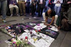 A man writes on a makeshift memorial as fans gather at Harlem's Apollo Theater to celebrate the life of Prince in Manhattan. REUTERS/Andrew Kelly