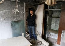 Roman Chernyavskiy, 32, poses for a photograph in his flat which was evacuated after an explosion at the Chernobyl nuclear power plant, in the ghost town of Pripyat, Ukraine April 18, 2016.  REUTERS/Gleb Garanich