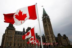 Canadian flags line the road around Parliament Hill during the National Day of Honour ceremony in Ottawa May 9, 2014. The event marks the end of Canada's military mission in Afghanistan. REUTERS/Blair Gable