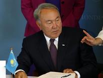 Президент Казахстана Нурсултан Назарбаев подписывает документы о вступлении страны в ВТО в офице организации в Женеве 27 июля 2016 года. Назарбаев в четверг приостановил земельную реформу, недовольство которой вывело на улицы сотни людей по всей центральноазиатской стране размером с Западную Европу. REUTERS/Denis Balibouse